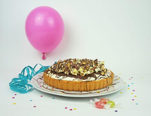 Torte mit Quarkcreme, darauf Popcorn, Kuvertüre und BonbonSplitter
