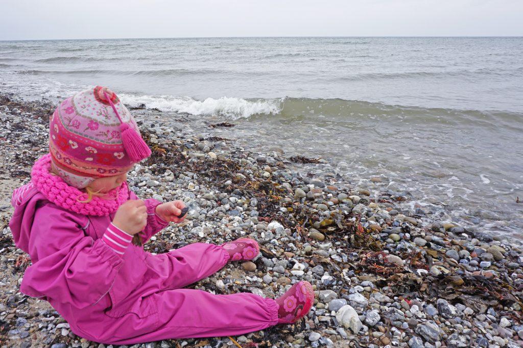 Kind am Meer mit Steinen
